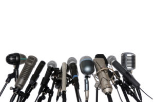 Various microphones aligned at press conference isolated over a white background